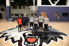 Education and Basketball Enrichment Program winners pose for a photo on the Wolves practice court.