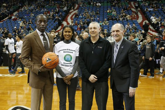 Minnesota Timberwolves general manager Milt Newton, left, and wife Shalaun pose for photo with a representative from Sun Country Airlines and Timberwolves President Chris Wright, right, prior to an NBA basketball game against the Brooklyn Nets, Saturday, March 5, 2016, in Minneapolis. The Newtons were recognized after hosting six children from the Virgin Islands as part of their Emerald Gems Foundation. (AP Photo/Stacy Bengs)